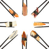 Sushi Circle. 8 different types of sushi being held up in in a circle formation with black chopsticks isolated on white Stock Photos