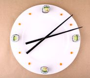 Sushi clock, time concept with caviar on a white plate Stock Photos