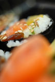 Sushi closeup. Closeup of a piece of delicious Japanese Maki Sushi roll with sesame seeds Royalty Free Stock Image