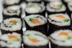 Sushi Closeup 2. Homemade sushi, made with rice, smoked salmon or surimi, avocado and cucumber Royalty Free Stock Images