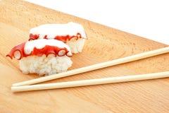 Sushi com os chopsticks do polvo e da madeira imagem de stock