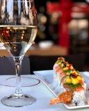 Sushi com salmões e milho em uma placa branca e em um vidro da água imagens de stock