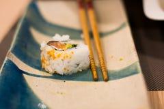 Sushi com varas chinesas em uma placa Imagem de Stock