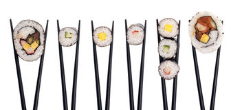 Sushi Combo #2. Five pieces of sushi in a row being held up with black chopsticks isolated on a white background Royalty Free Stock Photo