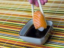 Sushi con il salmone sottilmente affettato su riso su un fondo immagini stock libere da diritti