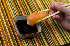 Sushi con il salmone su un servizio del riso sui precedenti di una tela di bambù fotografia stock libera da diritti