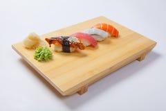 Sushi con il salmone su un vassoio di legno Immagini Stock