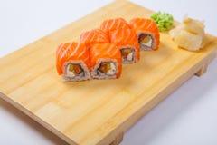 Sushi con il salmone su un vassoio di legno Immagine Stock