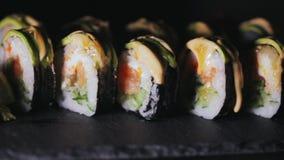 Sushi con las rebanadas de pepinos de color salmón y frescos Sushi apetitoso en un tablero de piedra negro Primer almacen de metraje de vídeo