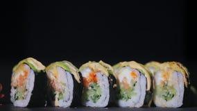 Sushi con las rebanadas de pepinos de color salmón y frescos Sushi apetitoso en un tablero de piedra negro Primer almacen de video