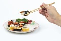 Sushi con los palillos, escogidos a mano. imagenes de archivo
