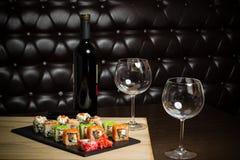 Sushi con vino rosso su una tavola al ristorante Immagini Stock