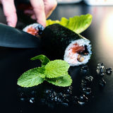 Sushi cook cutting rolls on a black table Stock Photography