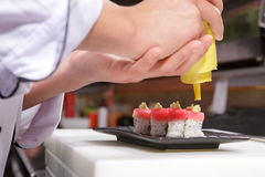 Sushi cook pours sauce Stock Photography