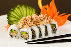 Sushi Crab Roll. Fancy crab and shrimp tempura roll with avocado on a white plate garnished with sliced cucumber and carved carrots Stock Images