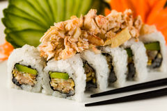 Sushi Crab Roll. Fancy crab and shrimp tempura roll with avocado on a white plate garnished with sliced cucumber and carved carrots Royalty Free Stock Photography