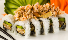 Sushi Crab Roll. Fancy crab and shrimp tempura roll with avocado on a white plate garnished with sliced cucumber and carved carrots Royalty Free Stock Images