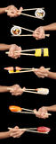 Sushi criss-cross. Set of 7 hands holding various types of sushi with chopsticks isolated on a black background Stock Photos