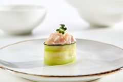 Exquisite Asian menu in the restaurant. Sushi in cucumber with sea bass with fresh herbs on  white plate with  gold border. Asian restaurant menu Stock Photography