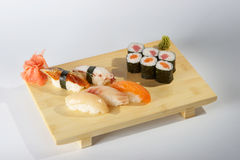 Sushi on cutting board. Fresh sushi roll on wooden chopping or cutting board; studio background Stock Photo