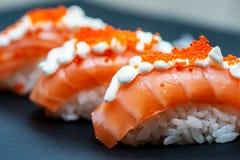 Sushi d?licieux et juteux avec le plan rapproch? saumon? de riz et de caviar sur un noir photographie stock