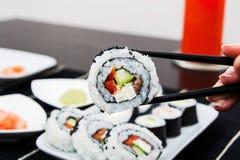 Sushi da terra arrendada da mão em varas Fotografia de Stock