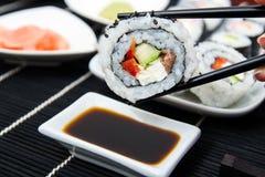 Sushi da terra arrendada da mão em varas Foto de Stock Royalty Free