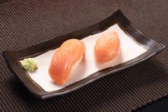 Sushi de color salmón con wasabi en el plato de cerámica, salmón con arroz de sushi Fotografía de archivo
