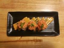 Sushi de color salmón de la fusión, materia con el pepino, palillo y mango, comida del cangrejo del estilista Fotos de archivo libres de regalías