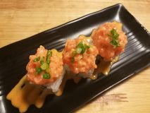 Sushi de color salmón de la fusión, materia con el pepino, palillo y mango, comida del estilista, tiro medio del cangrejo Imagen de archivo libre de regalías