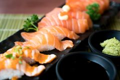 Sushi de color salmón mezclado en la placa negra junto con la salsa japonesa y Foto de archivo libre de regalías
