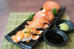 Sushi de color salmón mezclado en la placa negra junto con la salsa japonesa y Foto de archivo