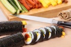 Sushi de coupe avec les ingrédients et le fond de couteau Photo stock