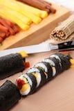 Sushi de coupe avec les ingrédients et le fond de couteau Photographie stock libre de droits