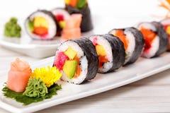 Sushi de Futomaki dans une rangée avec le wasabi et le gingembre Images stock
