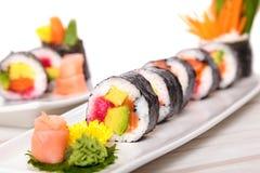 Sushi de Futomaki dans une rangée avec le wasabi et le gingembre Image libre de droits