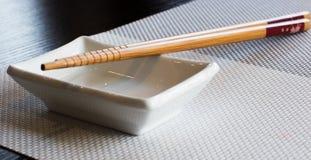 Sushi de los palillos con la taza Foto de archivo libre de regalías
