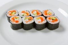Sushi de maki d'avocat de saké d'un plat blanc Photo stock