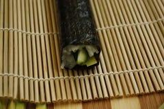 Sushi de Maki préparés en roulant l'algue, le riz et les poissons de nori sur le tapis en bambou de makisu photo stock