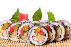 Sushi de Maki sur le tapis avec le fond blanc Photo stock