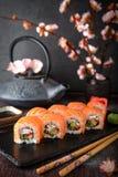 Sushi de petit pain de Philadelphie avec des saumons, concombre, avocat, fromage fondu, caviar de tobiko Menu de sushi photographie stock libre de droits