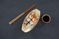Sushi de plat formé par bateau avec des baguettes Photographie stock