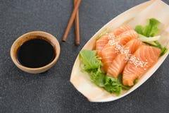 Sushi de plat formé par bateau avec des baguettes Images stock