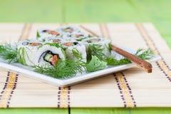 Sushi de Uramaki con el pepino, los salmones crudos y el eneldo Foto de archivo libre de regalías