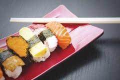 Sushi de variété avec des baguettes au-dessus de la table Image stock