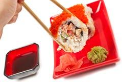 Sushi della holding della mano degli uomini Immagini Stock