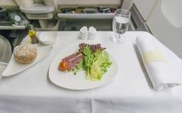 Sushi determinado de la comida de aviones en una bandeja, en una tabla blanca Imagenes de archivo
