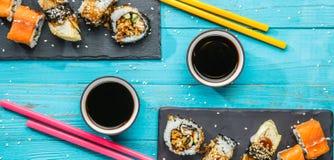 Sushi, di bastoni colorati multi alla tavola Fotografia Stock Libera da Diritti
