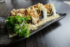 Sushi di color salmone del rotolo con farina croccante e salsa ed aglio del wasabi con coriandolo Fotografie Stock