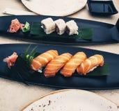 Sushi di color salmone di nigiri, accanto ai rotoli sulle foglie in bande nere - cucina giapponese di maki con la salsa di soia e fotografie stock libere da diritti